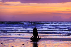 Silhouette young woman doing yoga on the beach at sunset Stock Photos