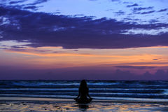 Silhouette young woman doing yoga on the beach at sunset Stock Image