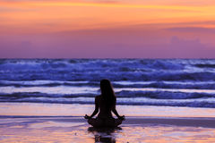 Silhouette young woman doing yoga on the beach at sunset Royalty Free Stock Photography
