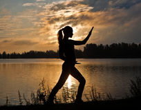 Silhouette of a young woman doing yoga exercise. Silhouette of a beautiful woman doing yoga exercise on the riverside Royalty Free Stock Images