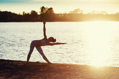 Silhouette of a Young woman doing yoga exercises on the lake beach at sunset stock photography