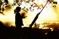 Silhouette of a young woman drawing a picture on an easel on nature, female standing under tree with brush and artist`s palette stock image