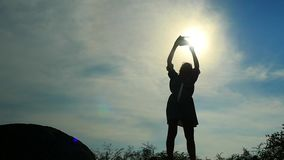 Silhouette of young woman in dress standing on the rock and takes a picture with mobile phone. slow motion. 1920x1080 stock footage