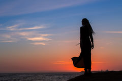 Silhouette of young woman in dress standing by the sea Stock Image