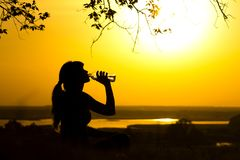 Silhouette of a woman drinking water after fitness training in nature, female profile at sunset, concept of sport and relaxation. Silhouette of a young woman Royalty Free Stock Photos