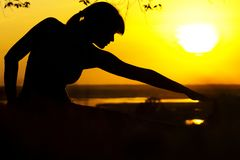 Silhouette of a woman engaged in fitness in nature at sunset, a sports female profile, the concept of sport and relaxation Royalty Free Stock Images