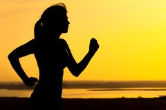 Silhouette of a woman jogging on nature at sunset, sports female profile, concept of sport, leisure and healthcare Stock Image