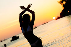 Silhouette of young woman enjoying summer beach vacation a Royalty Free Stock Photo