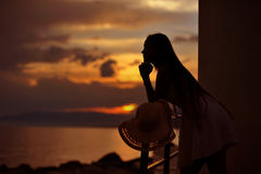 Silhouette of Young woman at evening sunset. Silhouette of Young woman on evening sunset sky background Royalty Free Stock Photos