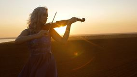 Silhouette of a young woman figure in the sunrays playing the violin, girl relaxing and moving bow along the strings of a musical. Young beautiful woman plays stock footage