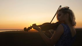 Silhouette of a young woman figure in the sunrays playing the violin, girl relaxing and moving bow along the strings of a musical. Young beautiful woman plays stock video footage