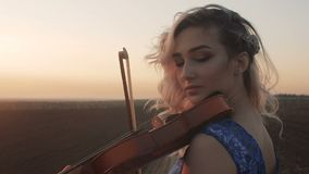 Silhouette of a young woman figure in the sunrays playing the violin, girl relaxing and moving bow along the strings of a musical stock video