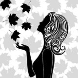 Silhouette of young woman with flying leaves Stock Images