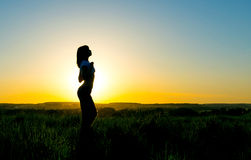 Silhouette young woman in front of a beautiful sunset Stock Photography