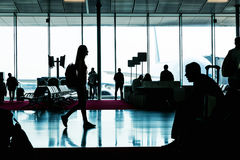 Silhouette of young woman going in waiting hall. royalty free stock photo