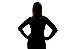 Silhouette of young woman with hands on hip Stock Photos