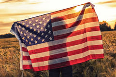 Silhouette of Young Woman Holding USA Flag in Field at Sunset Stock Images