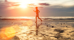 Silhouette of a young woman jogger at sunset on the seashore. Sport. Royalty Free Stock Image