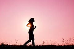 Silhouette young woman jogging with sunset Royalty Free Stock Photo