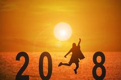 2018 news year. Silhouette of young woman jumping on the beach between 2018 years with beautiful sunset at the sea, concepts of news year and business target Stock Images