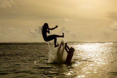 Silhouette of young woman jumping out of ocean Royalty Free Stock Images