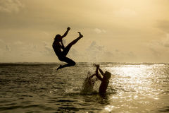 Silhouette of young woman jumping out of ocean Royalty Free Stock Photography