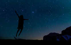 Silhouette of young woman jumping over sand hill, beneath the star Royalty Free Stock Photography