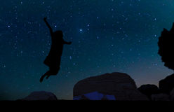 Silhouette of young woman jumping over sand hill, beneath the star Royalty Free Stock Images