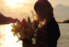 Silhouette of a young woman with lilies stock image