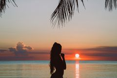 Silhouette of young woman with long hair  in bikini on amazing tropical sunset stock photography