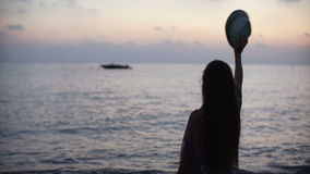 Silhouette of a young woman with long hair waving hat against sea at sunset stock video footage