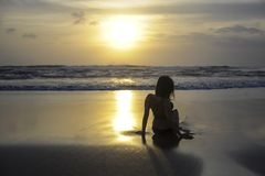 Silhouette of young woman lying on sand looking to sea sunset horizon with beautiful sun. And dramatic orange sky at dawn in Asian beach in tourism vacation and Royalty Free Stock Photo