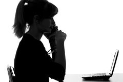 Silhouette of a young woman makes a purchase order by phone on the Internet Stock Photography