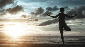 Silhouette of young woman meditating on the ocean beach Stock Photo