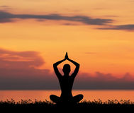 Silhouette of a young woman meditating on the sunset Royalty Free Stock Photo