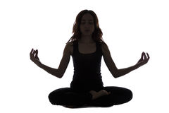 Silhouette of a young woman in meditation pose Stock Image