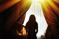 Silhouette of a young woman opens curtains at window Stock Photo