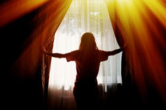 Silhouette of a young woman opens curtains at window.  Royalty Free Stock Photos