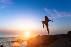 Silhouette of a young woman performing fitness exercises on the sea coast. During amazing sunset Royalty Free Stock Image