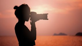 Silhouette of young woman photographer, taking pictures of landscape at sunset. In Thailand royalty free stock photography