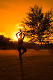 Silhouette young woman play yoga on the beach. With sunlight Stock Photos