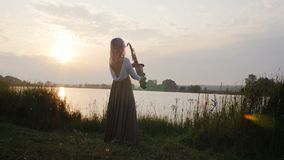 Silhouette of a young woman playing on the saxophone near the riverbank at dawn, a beautiful girl in a long dress with a wind musi. Cal instrument in nature, a stock video footage