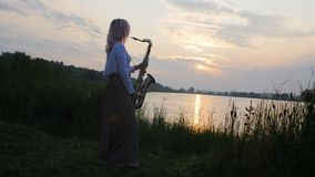 Silhouette of a young woman playing on the saxophone near the riverbank at dawn, a beautiful girl in a long dress with a wind musi. Cal instrument in nature, a stock video