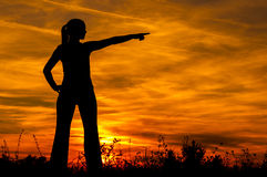 Silhouette of the young woman pointing to something in the distance. At sunrise Stock Image