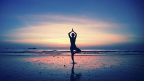 Silhouette of young woman practicing yoga on the beach at amazing sunset. Meditation Stock Photography