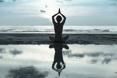 Silhouette young woman practicing yoga on the beach Stock Images