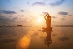 Silhouette young woman practicing yoga on the beach sea at sunset. Royalty Free Stock Image
