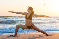 Silhouette of a young woman practicing yoga on the beach at sunrise. Sport, wellness concept Royalty Free Stock Photos