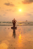 Silhouette young woman practicing yoga on the beach Royalty Free Stock Photography