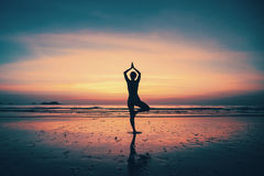 Silhouette young woman practicing yoga on the beach. At sunset Royalty Free Stock Photos